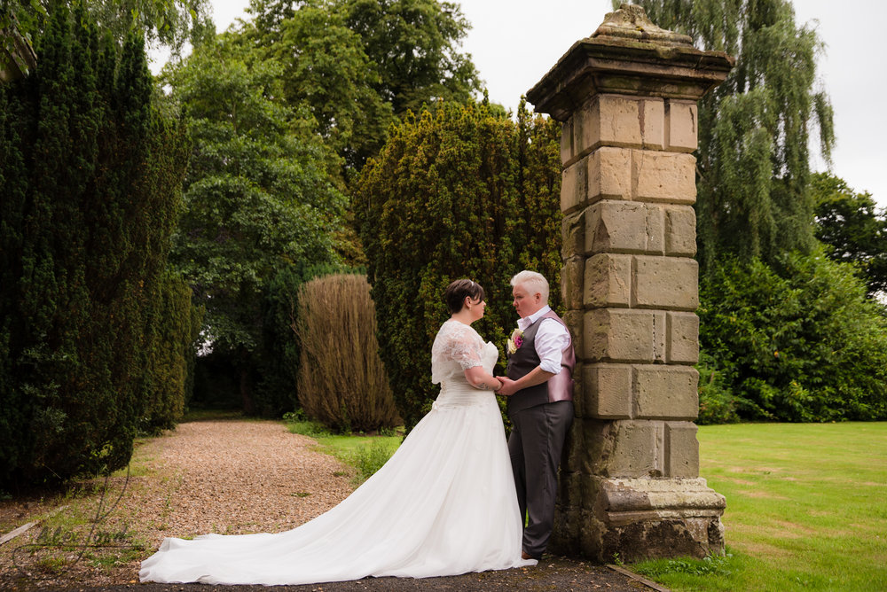 the bride and bride stand outside the gates of albrighton hall chatting together during their wedding photography