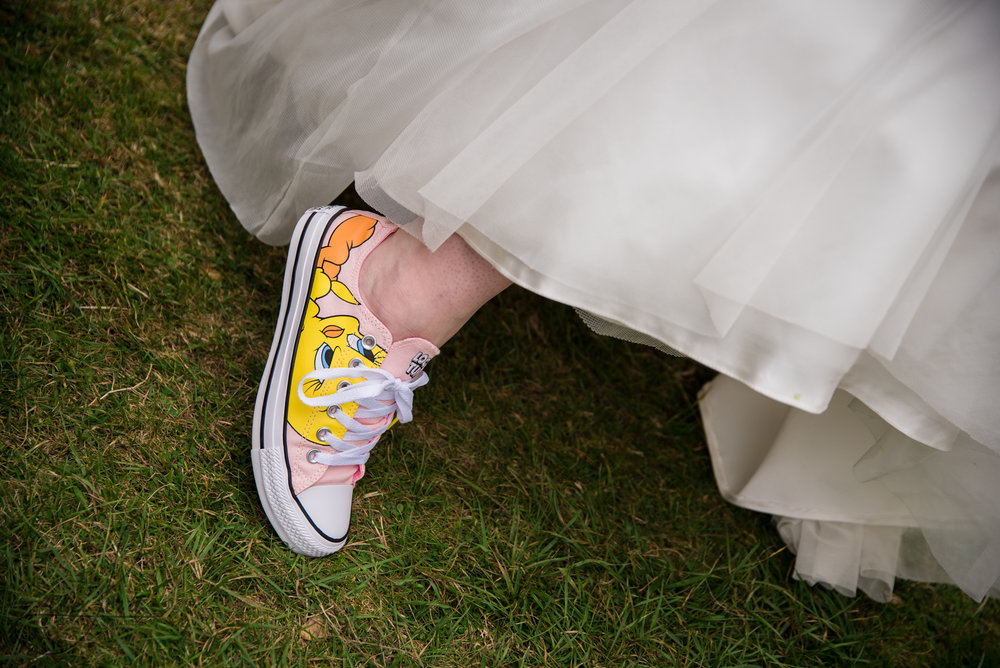 the bride shows her converse shoes to the camera