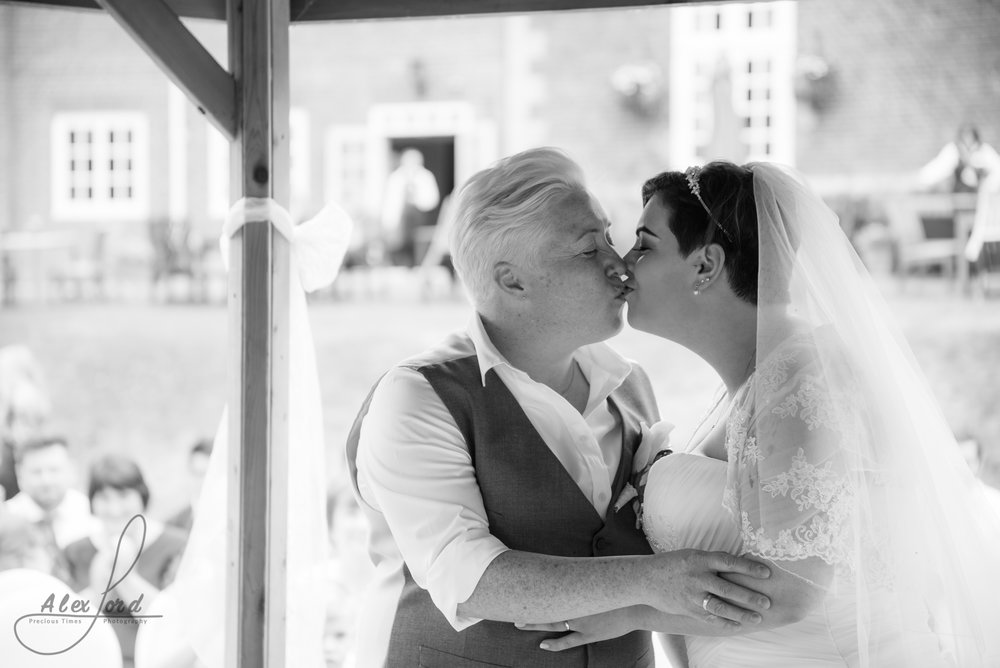 the bride and bride share their first kiss as a married couple
