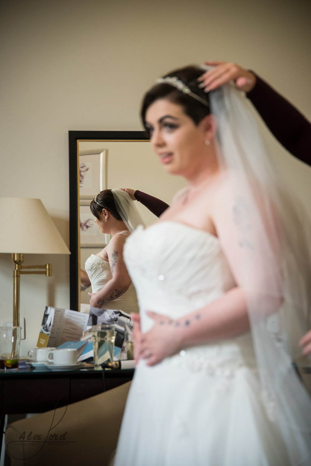 the bride has her veil fitted just before heading down for the wedding ceremony