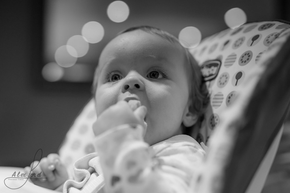 a young baby sits chewing on her fingers before the wedding ceremony
