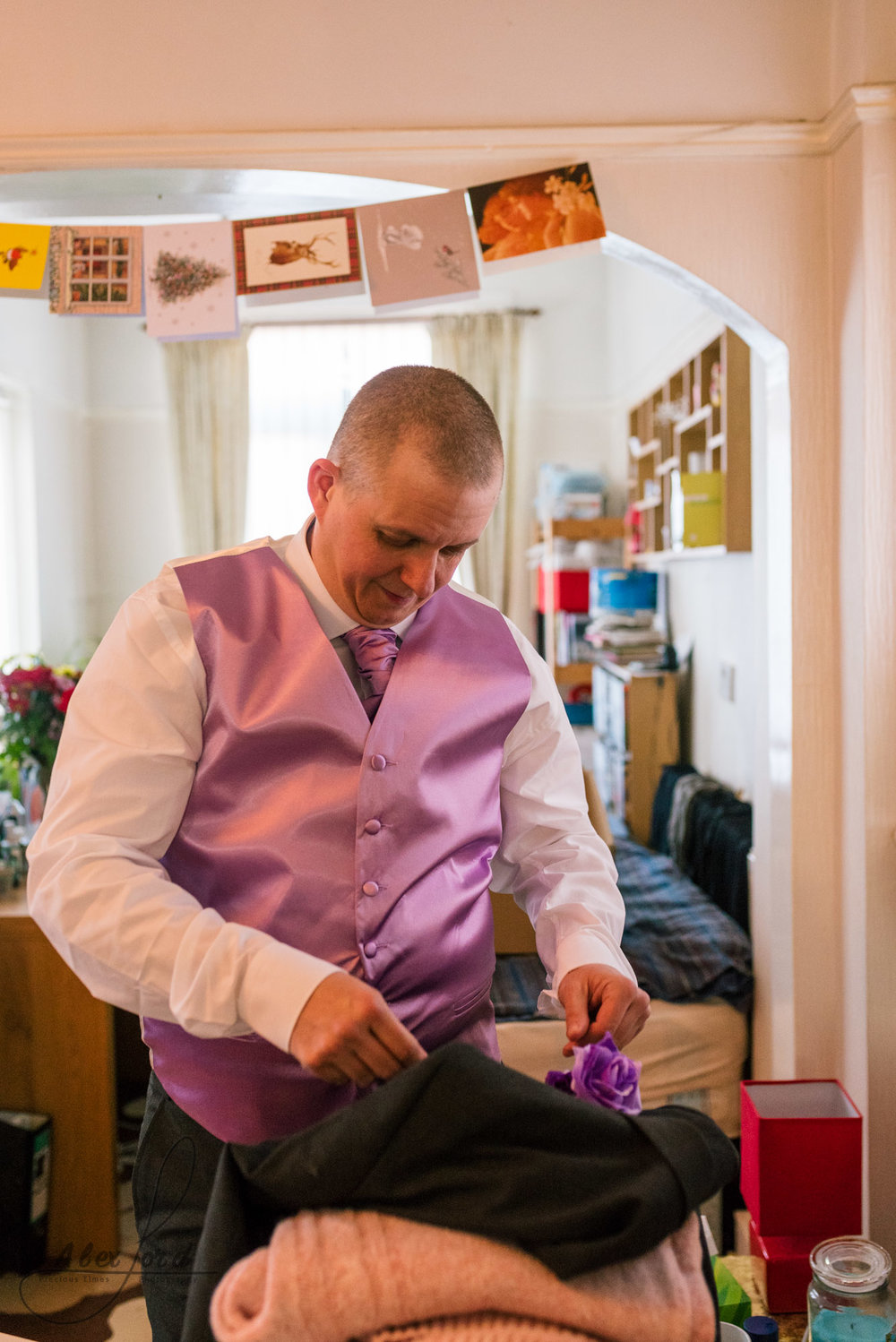 the best man make some finishing touches to his suit before him and the groom leave for the wedding ceremony in liverpool