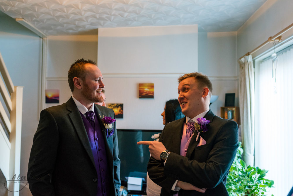 the groom and the best man have a laugh together in the middle of the living room before leaving for the wedding ceremony