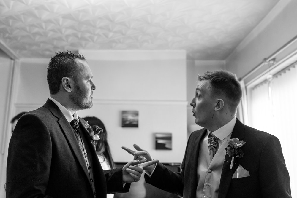 the bride and his best man stand chatting in the middle of the living room