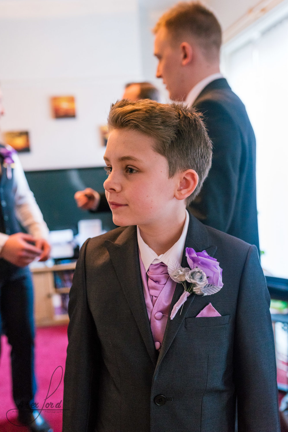 a young usher dressed in a suit and a pink and purple tie looks into the middle of the living room