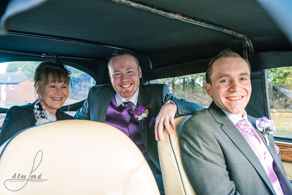 the groom sits in the wedding car with his mum and dad. The groom is in the back seat of the car