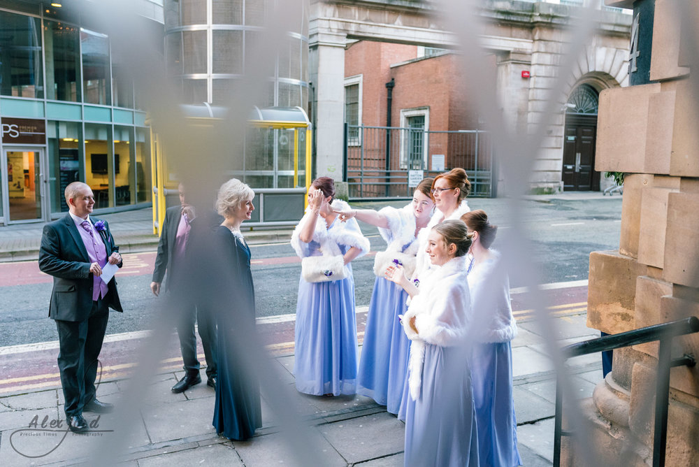 the bridesmaids stand outside the richmond hotel in liverpool awaiting the arrival of the bride
