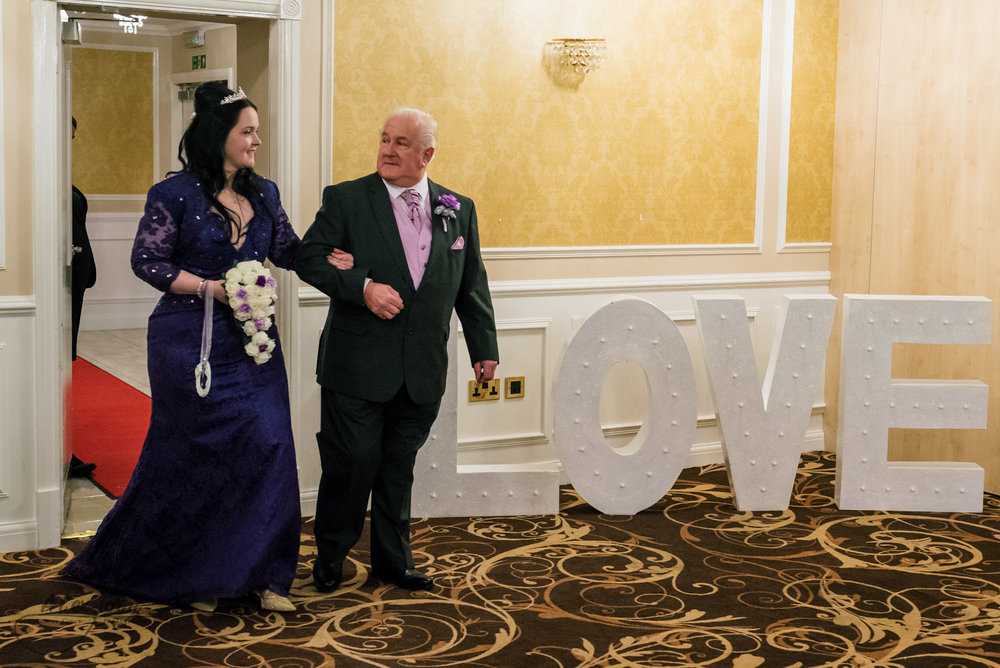 the bride and her father make an entrance into the wedding ceremony room