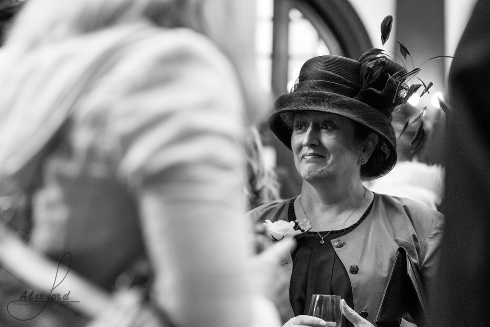 woman in a very large hat stands and chats to another guest at the wedding reception welcome drinks