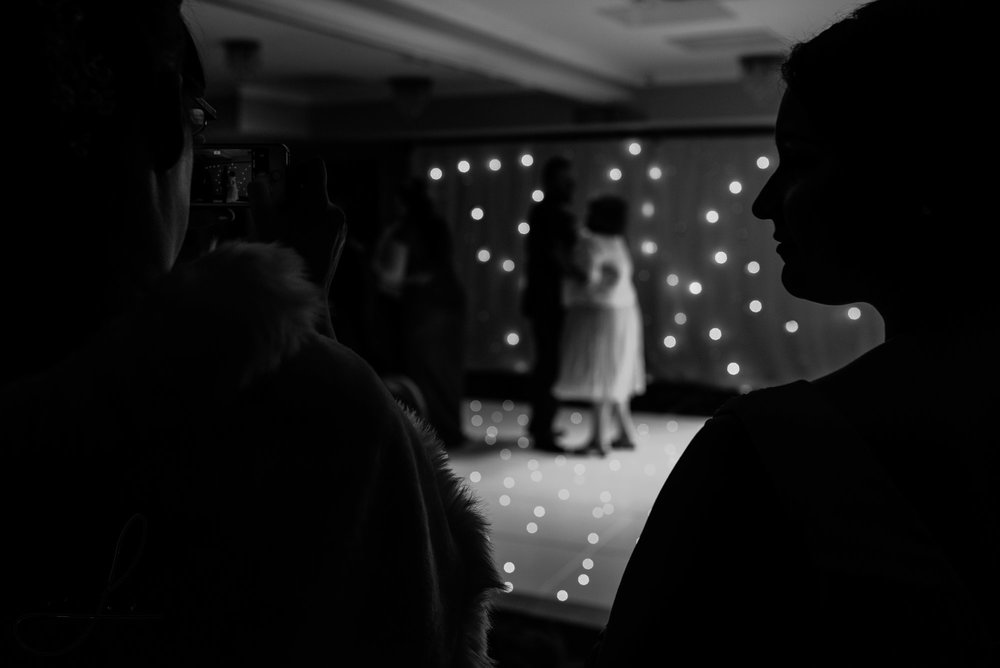a black and white image of wedding guests on the dance floor, lit up with fairy lights