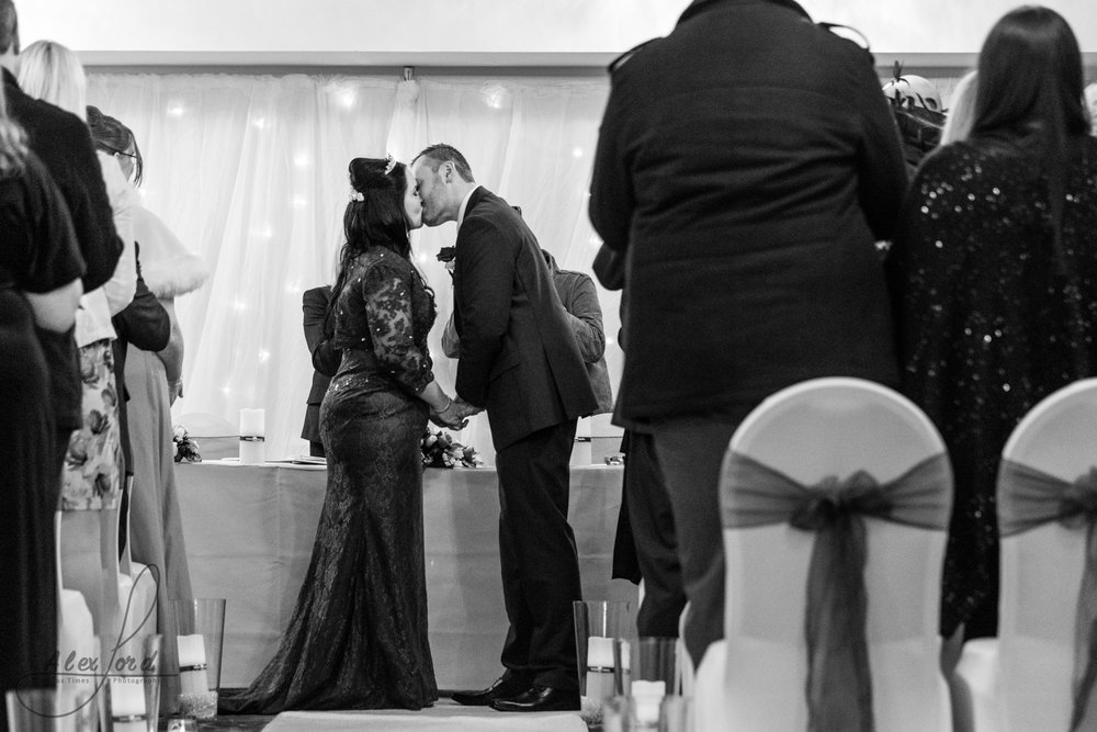 the bride and groom share a kiss during their wedding ceremony