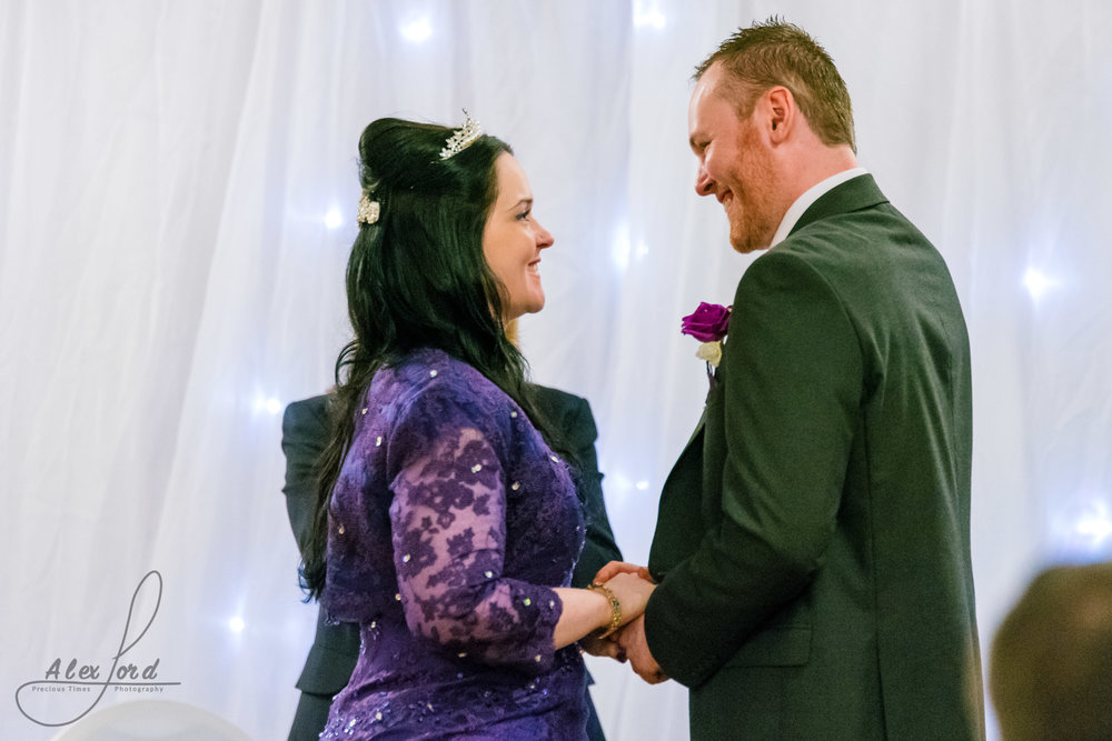 the bride and groom look lovingly at each other during their wedding vows