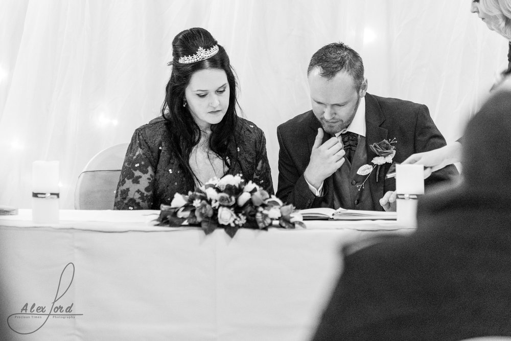 the bride and groom sit and sign the marriage register