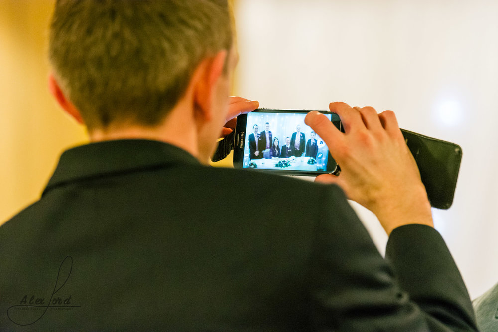 a wedding guest takes a photo of the signing of the register from his seat