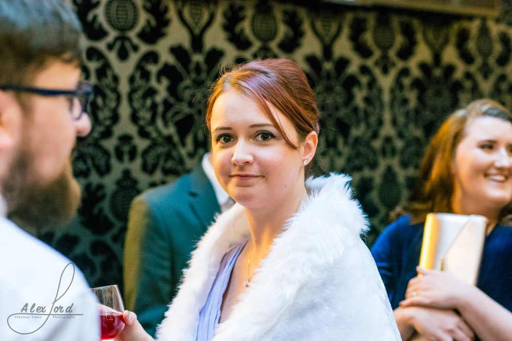 a female wedding guest poses for the camera during the welcome drinks
