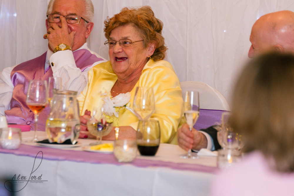 the brides mother and father have a giggle during the wedding speeches