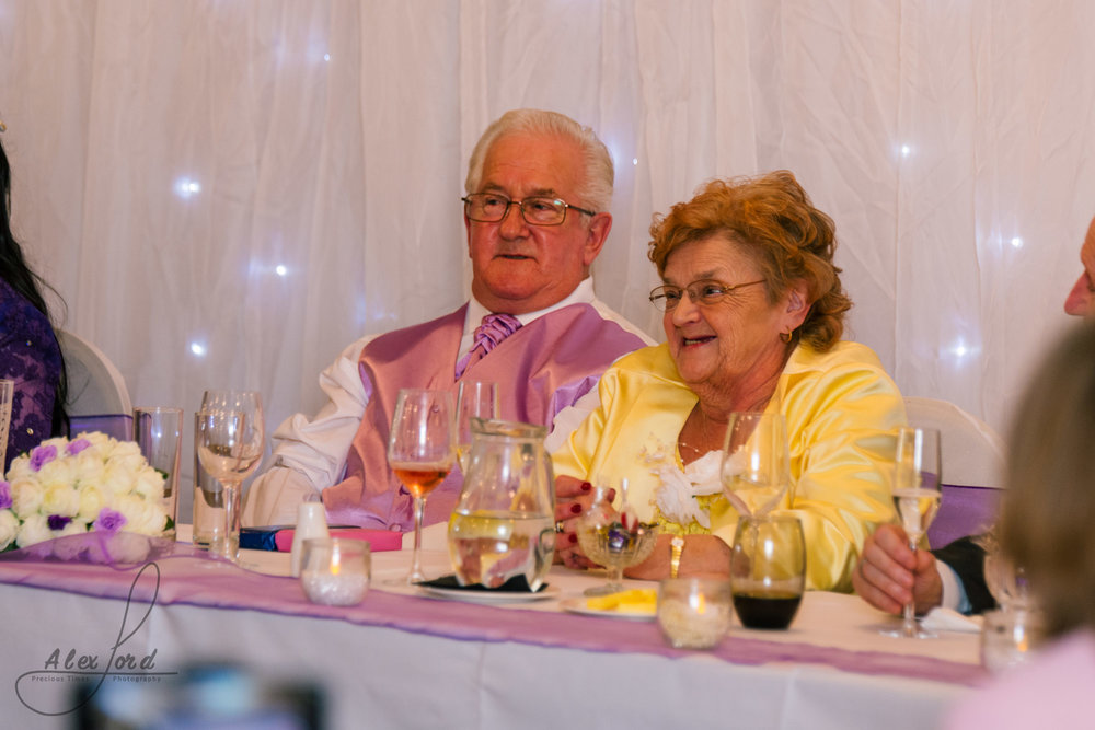 the brides mum and dad laugh out loud at a joke during the best mans speech