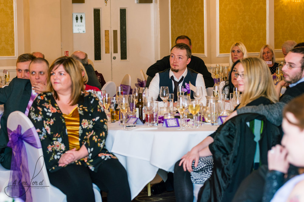 wedding guests sit and listen to the speeches