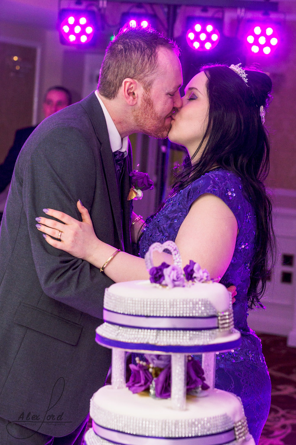 the bride and groom share a kiss just before they cut their wedding cake