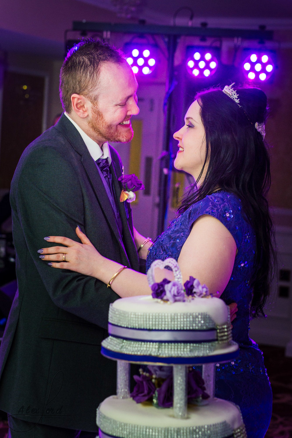 the bride and groom stand behind the wedding cake and pose for a photo