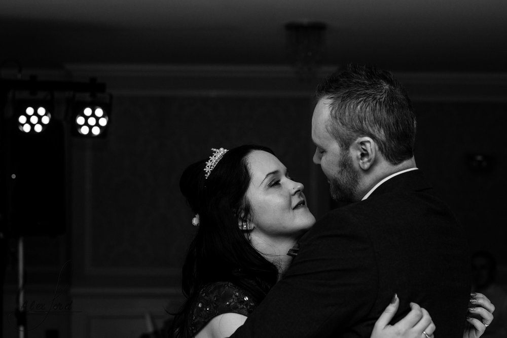 the bride and groom look into each others eyes during their first dance