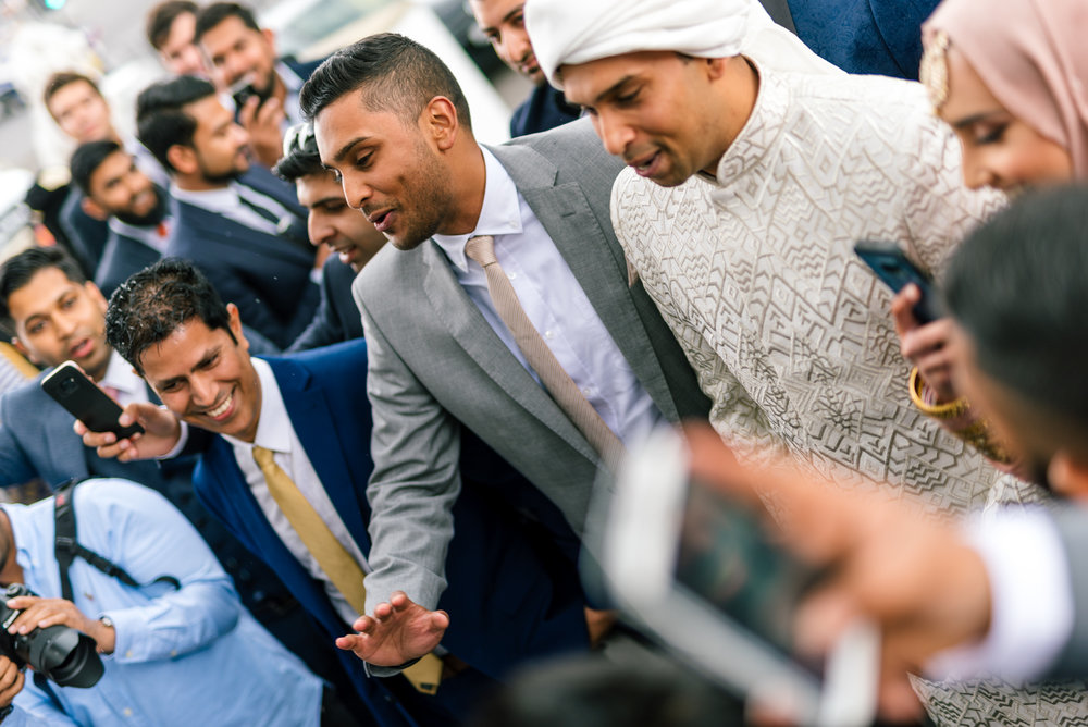 The groom and his friends start bartering with the brides family in order to be let in to the wedding venue