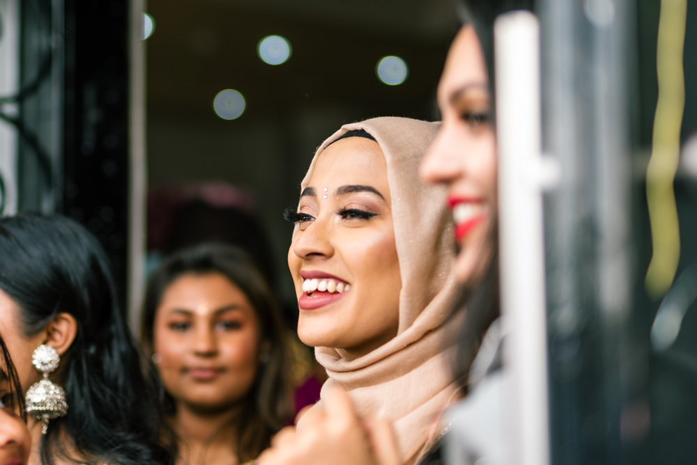 A member of the bride's family smiles happily as she awaits the entrance of the groom