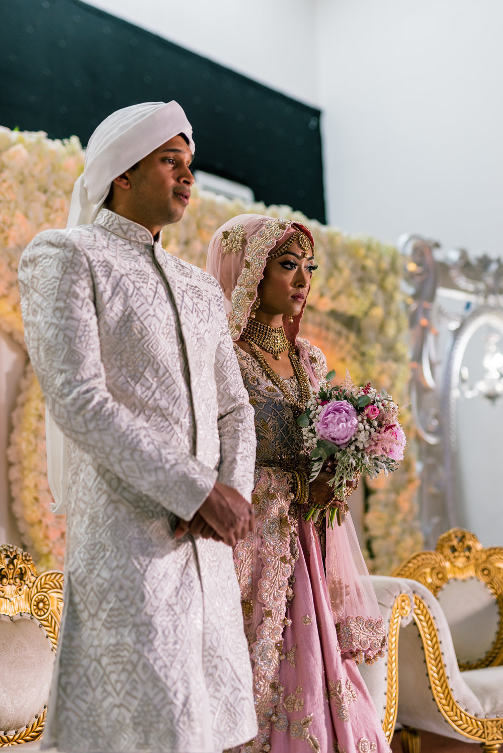 the bride and groom stand in front of their guests, waiting for the start of the wedding ceremony