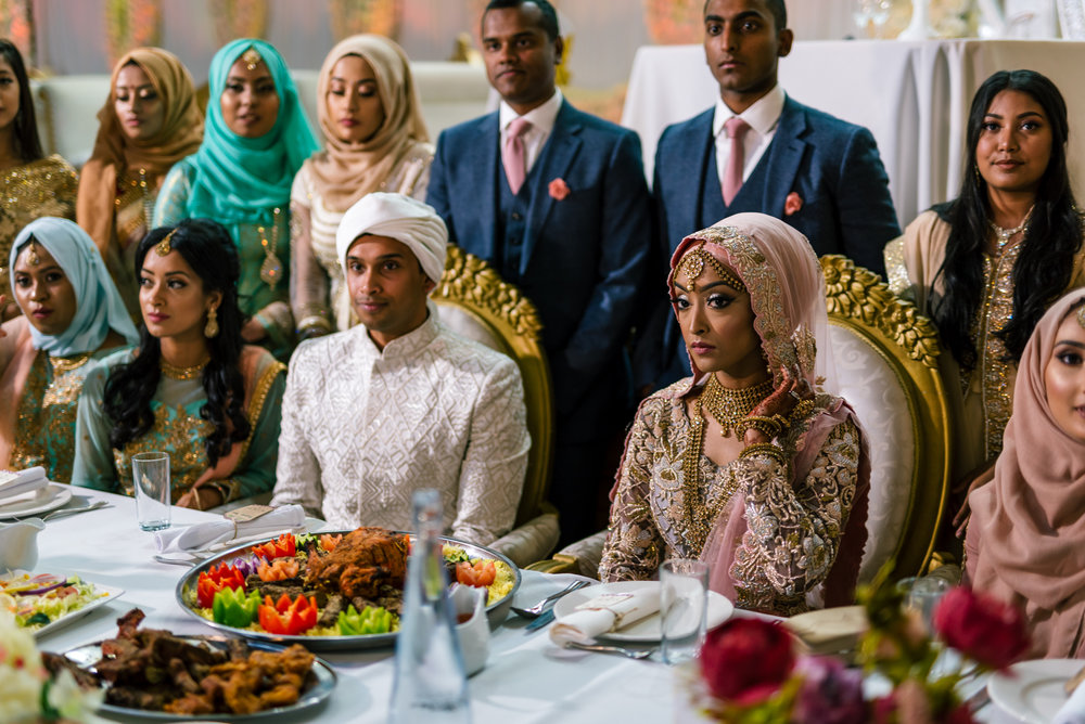 the bride and groom sit on their table with lots of indian food in front of them