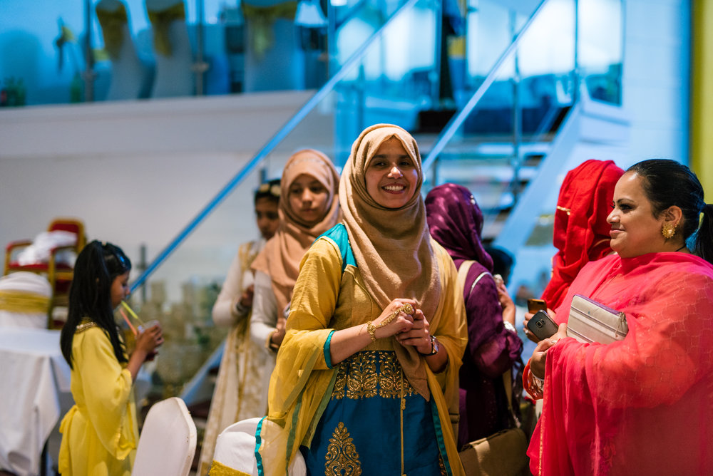 wedding guests dressed in beautiful traditional indian clothes chat to each other in the wedding venue