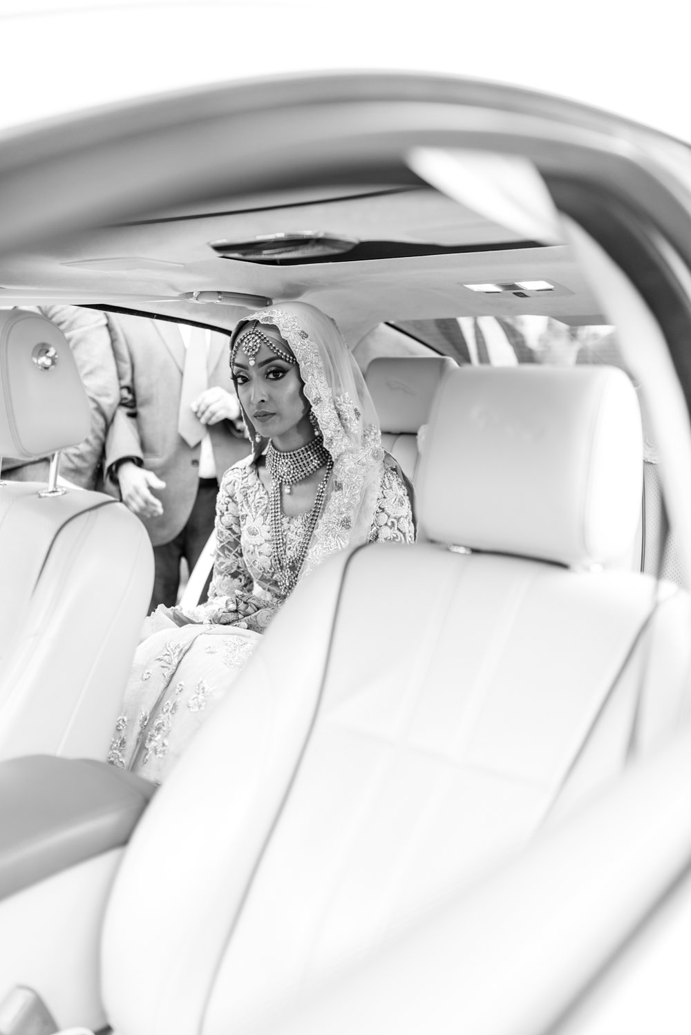 the bride sits in the car before the groom joins her to depart for their new life