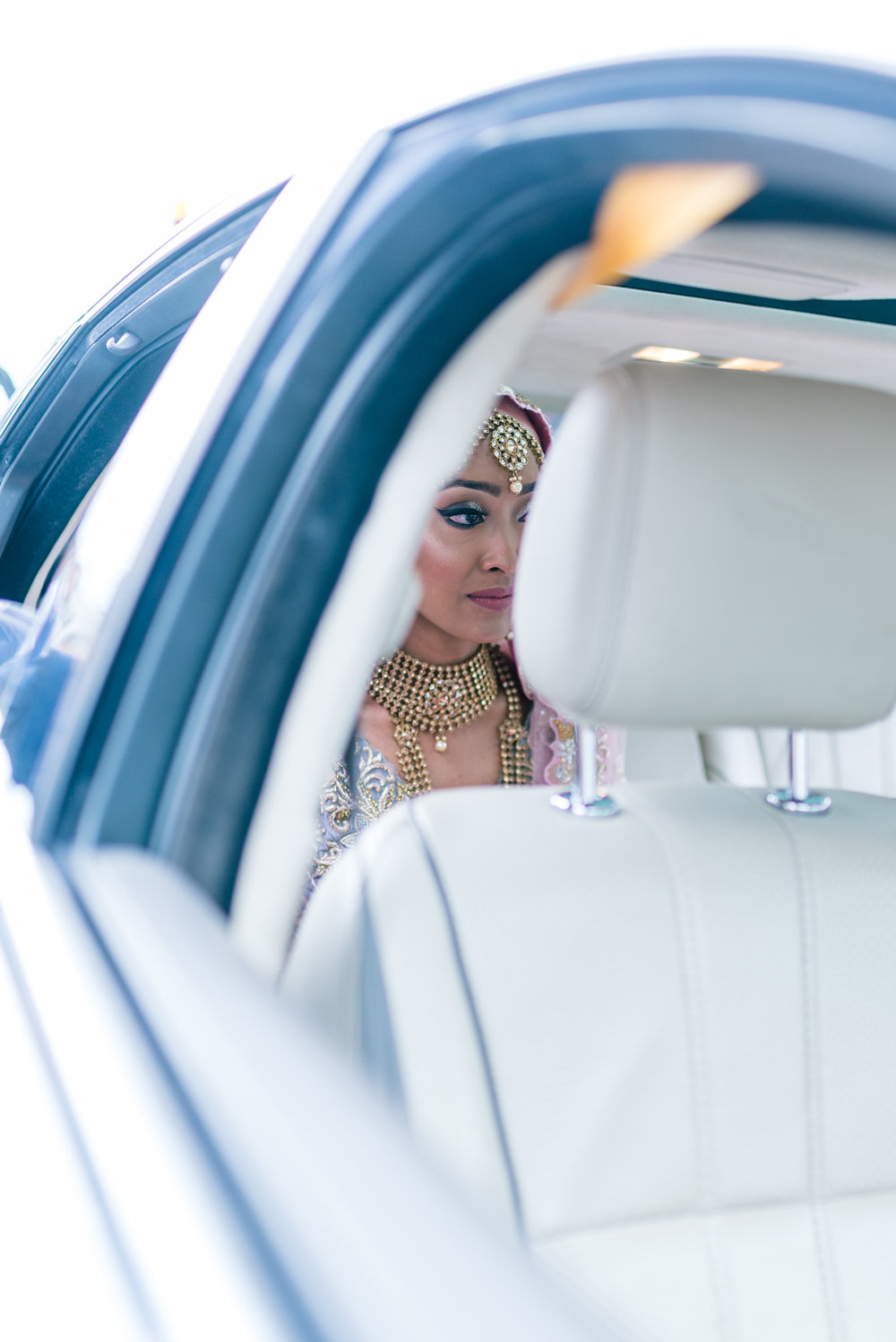 the bride sits contemplative in the back of the car while her groom sits in the front