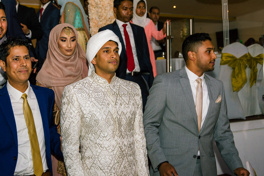 members of the grooms family escort the groom out of the wedding venue