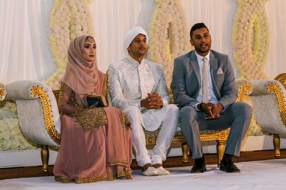 the bride, groom and the grooms brother sit on the stage for some family photos
