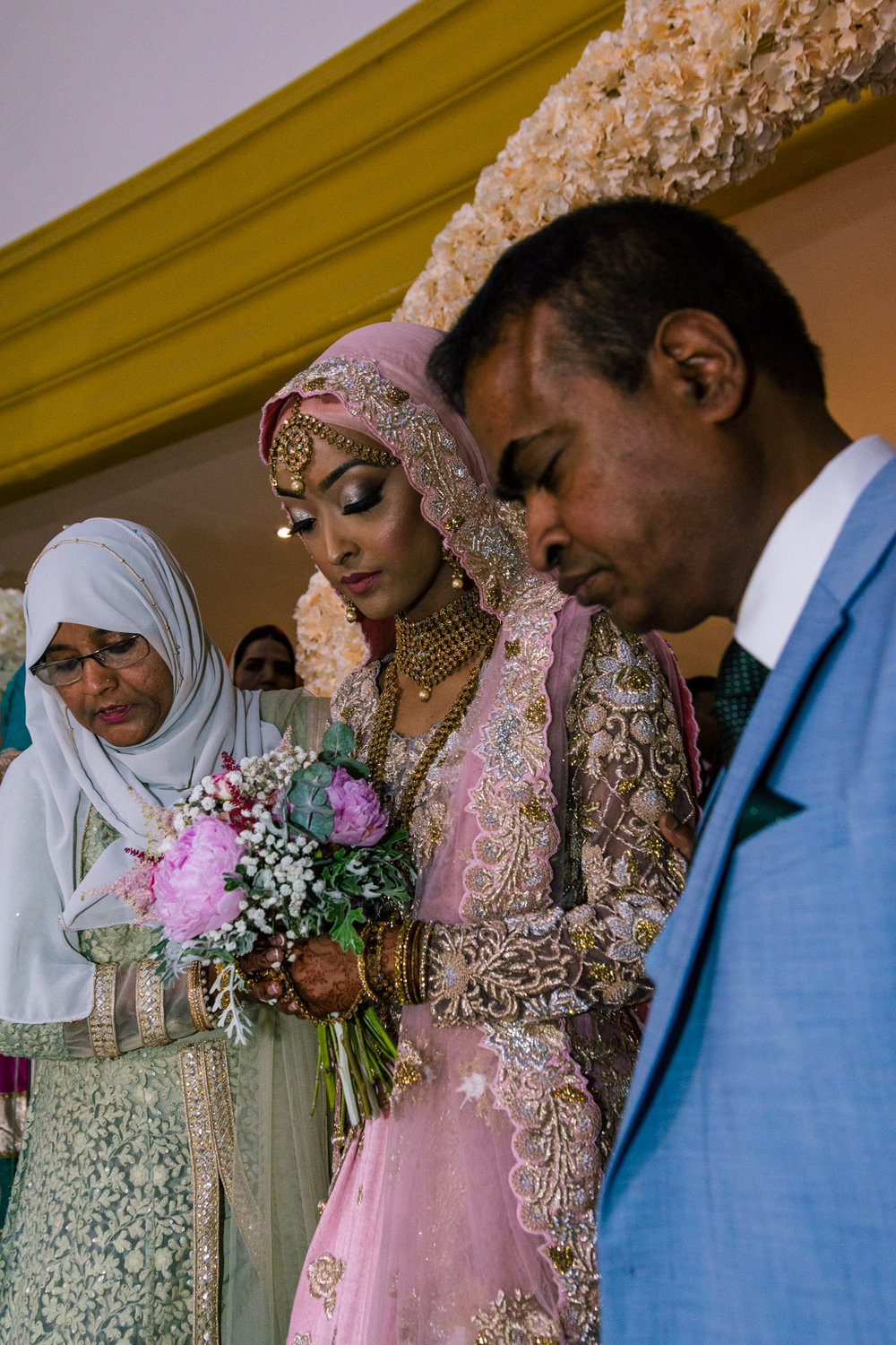 an emotional indian bride dressed in pink and gold with her father who is dressed in a stunning blue suit