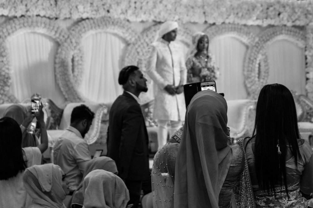 the bride and groom stand proudly facing all their friends and family on the stage