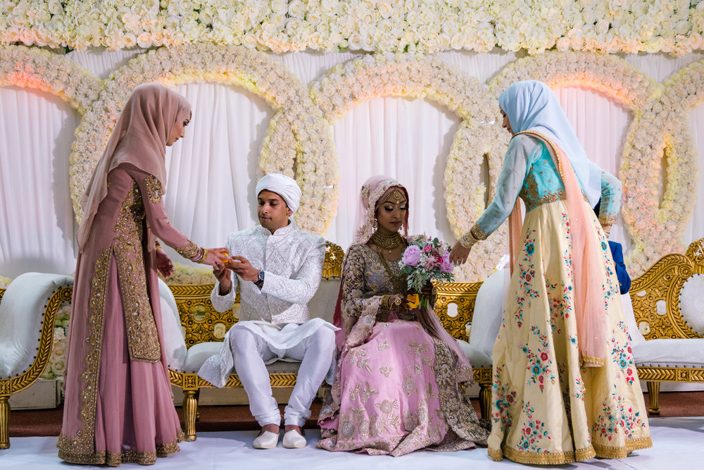 The bride and groom are presented with gifts from the brides sisters, they are dressed in traditional indian wedding clothes