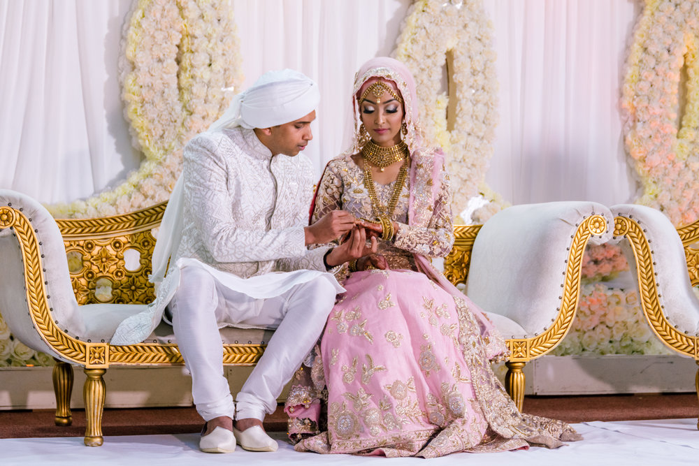 the bride and groom have a chat with each other whilst sitting on the stage in between official photos