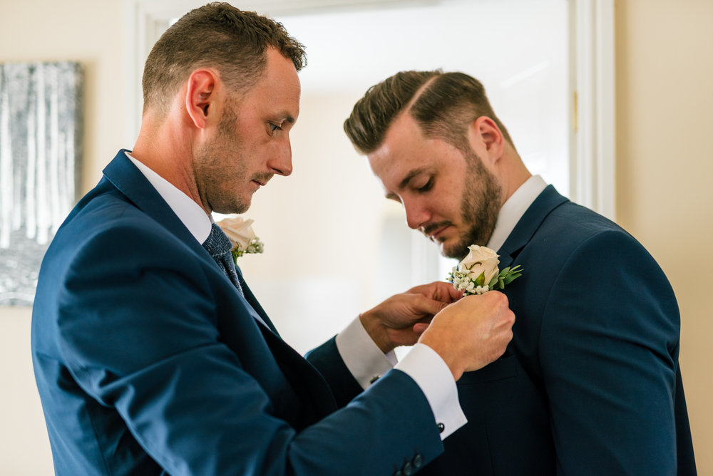 best man putting the flower on the grooms jacket