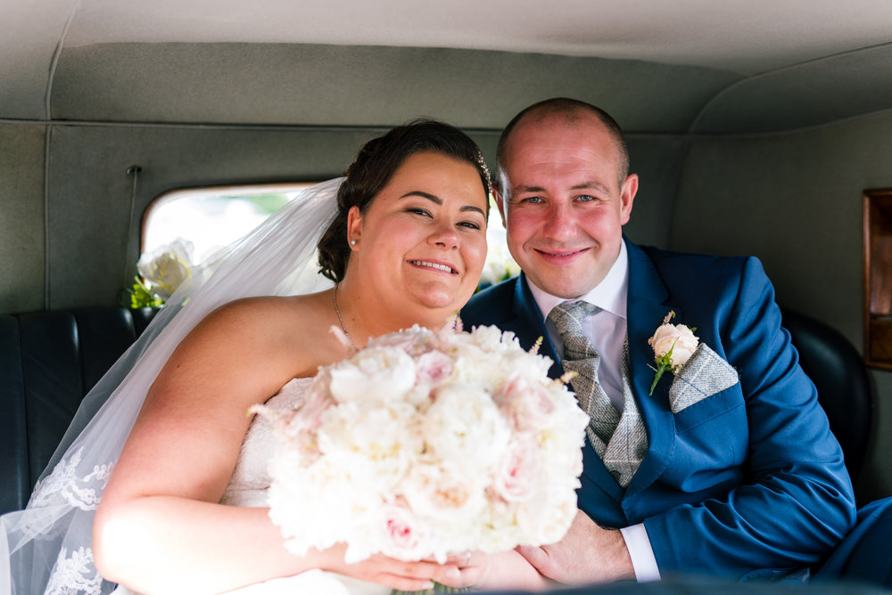 happy bride and groom inside the wedding car