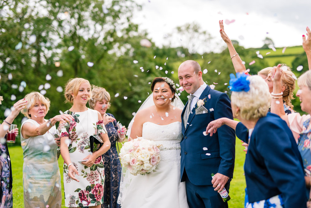 bride and groom get covered in confetti