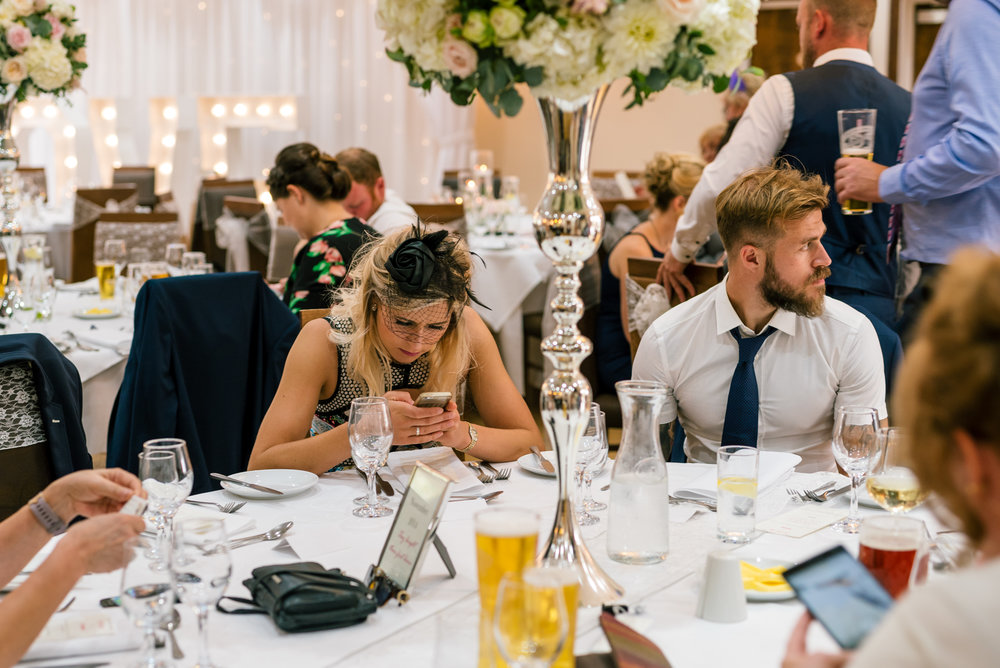 wedding guest lost in her phone