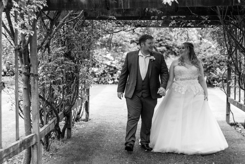 bride and groom walking in the grounds of nunsmere hall