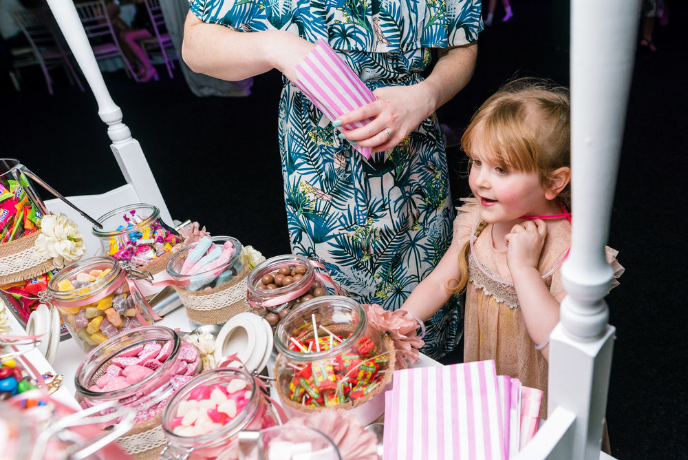 child getting sweets from the candy cart