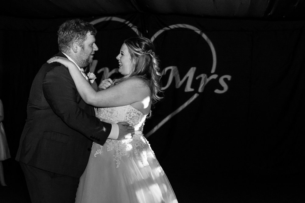 bride and grooms first dance with love letters behind them
