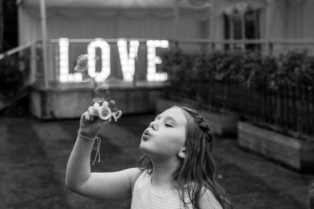 Flower girl blows bubbles