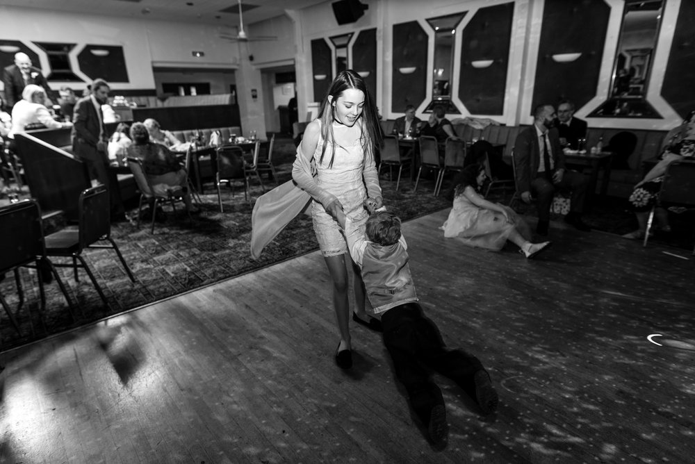 Two children, one spinning the other around on the dance floor.