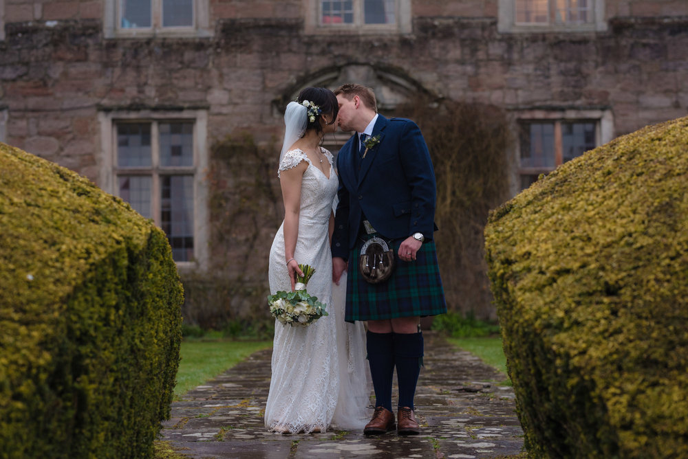 Bride and groom stand for a kiss in front of a damp Askham Hall.