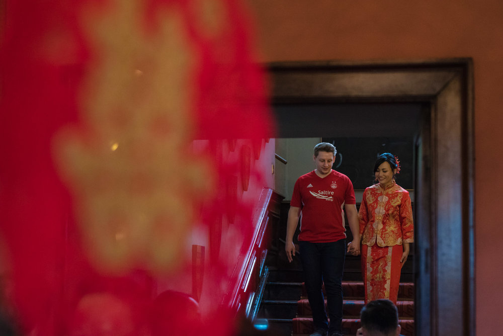 The bride and groom walk down the stairs of Askham Hall towards their Chinese tea ceremony.