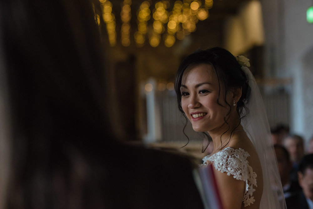 The bride shares a smile with the registrar during the wedding ceremony at Askham Hall.